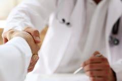 De hand van de artsenschok zoals hello met patiënt in bureau royalty-vrije stock foto