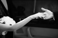 De hand van de bruid en de hand van de bruidegom terwijl het weggaan van de auto Stock Foto