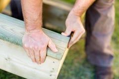 De Hand van de handarbeider het Bevestigen Hout bij Plaats Royalty-vrije Stock Afbeeldingen