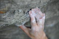 De hand van de klimmer van de rots op houvast Stock Afbeeldingen