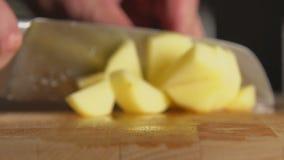 De hand van de kok snijdt een aardappel door een mes op een raad stock footage