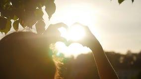De hand van de liefdevorm of Hart gevormd silhouet bij zonsondergang in langzame motie stock video