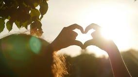 De hand van de liefdevorm of Hart gevormd silhouet bij zonsondergang in langzame motie stock videobeelden