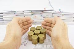 De hand van de mens beschermt stapel gouden muntstukken Royalty-vrije Stock Afbeeldingen