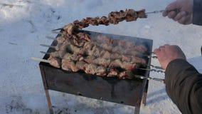 De hand van de mens inspecteert vleesplakken in saus op brand stock footage