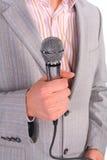De hand van de mens `s houdt microfoon stock afbeeldingen