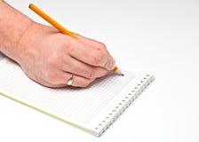De hand van de mens schrijft op een boek Stock Foto
