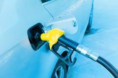 De hand van de mens vult brandstof bij benzinestation op royalty-vrije stock afbeeldingen