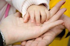 De hand van de moeder en van de baby van de vader Stock Afbeeldingen