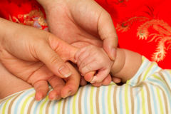 De hand van de moeder en van de vader en van de baby stock fotografie