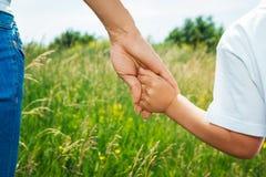 De hand van de moederholding van haar zoon Stock Afbeelding