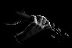 De hand van de musicus op de koorden van een viool in donkere kleuren Stock Afbeeldingen