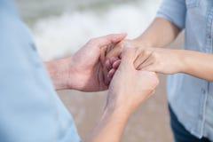 De hand van de paarholding door het strand Royalty-vrije Stock Foto