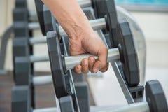 De hand van de sportmens houdt domoor, die het uitwerken uitoefenen bij fitness Royalty-vrije Stock Afbeeldingen