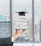 De hand van de student houdt een gadget met boeken en graduatiehoed op het Royalty-vrije Stock Foto