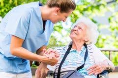 De hand van de verpleegstersholding van hogere vrouw in pensioenhuis stock afbeeldingen