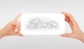 De hand van de volwassene en de hand die van het kind Witboek met abstract bosbeeld houden Witte achtergrond Stock Foto's