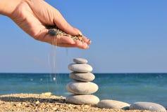 De hand van de vrouw bestrooit zand op kiezelsteenstapel Stock Fotografie