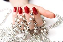 De hand van de vrouw en zilveren parels Stock Afbeeldingen