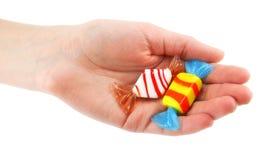 De hand van de vrouw geeft twee gekleurd suikergoed Royalty-vrije Stock Afbeelding