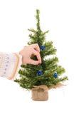 De hand van de vrouw hangt blauwe Kerstmisbal stock afbeeldingen