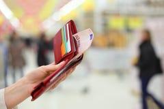 De hand van de vrouw houdt beurs met geld en creditcards Stock Fotografie
