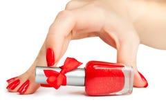 De hand van de vrouw met een fles rood nagellak stock fotografie