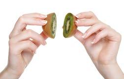 De hand van de vrouw met geïsoleerdx kiwifruit Stock Fotografie