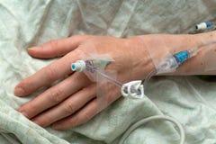De hand van de vrouw met intraveneuze naald en buizen Stock Foto's