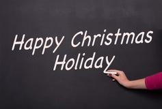 De hand van de vrouw met krijt op bord die gelukkige Kerstmis schrijven Stock Foto's