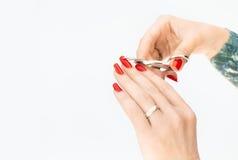 De hand van de vrouw met rode manicure scherpe spijkers met schaar stock foto