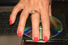 De hand van de vrouw met rode spijkers die DVD-schijf van PC nemen Stock Foto
