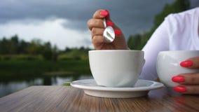 De hand van de vrouw met rood nagellak en een kop van koffie op de achtergrond van mooi landschap Close-up stock videobeelden