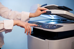 De hand van de vrouw met werkend kopieerapparaat Stock Foto's