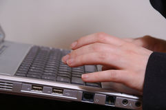 De hand van de vrouw op de sleutels van laptop stock afbeelding