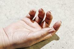 De hand van de vrouw op het asfalt Stock Afbeeldingen