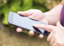 De hand van de vrouw wat betreft het scherm op slimme telefoon Stock Afbeeldingen