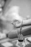 De hand van de vrouwelijke donor op armsteun met een helft-gevulde bloedzak Stock Fotografie