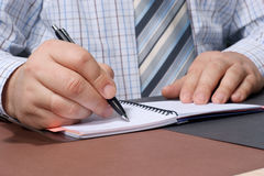 De hand van de zakenman met een pen die iets schrijft. Royalty-vrije Stock Fotografie