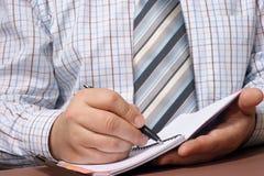 De hand van de zakenman met een pen die iets schrijft. Stock Foto's