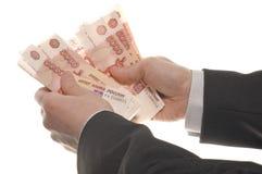 De hand van de zakenman met geld stock afbeelding