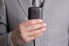 De hand van de zakenman met mobiele telefoon Stock Afbeeldingen