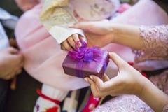 De hand van een baby die door vele mensen wordt omringd en giften ontvangt royalty-vrije stock afbeeldingen