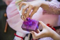 De hand van een baby die door vele mensen wordt omringd en giften ontvangt stock afbeeldingen