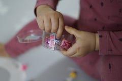 De hand van een baby wat betreft een klein stuk speelgoed met beide handen stock fotografie