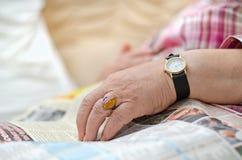 De hand van een bejaarde die op de krant liggen Stock Foto