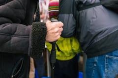 De hand van een bejaarde met een riet Een oude mens leunt op een stok Bedelaarsvoetganger op de straat De oude man hand is oud royalty-vrije stock afbeeldingen