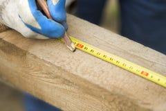De hand van een bouwvakker richt met een potlood de afstand op een houten rand Stock Afbeeldingen