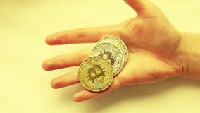 De hand van een jong meisje houdt een close-up van het bitcoinmuntstuk in een langzame motie Crypto munt in de handen van het mei stock video