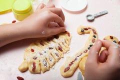 De hand van een kind maakt Kerstmiskoekjes van deeg in de vorm van een Kerstboom Voorbereidingen treffend voor Kerstmis, bakt een royalty-vrije stock foto